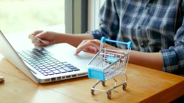 4 KB záběr. on-line bankovnictví, obchodní koncepce. samičí ruka držící kreditní kartu a nákupy online. Nakupování online pomocí kreditní karty v domácím životním stylu, nákupní košík v popředí