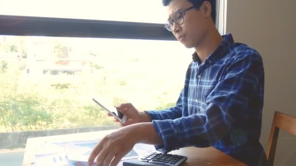 footage, serious Asian business man working with paper work and calculator for calculations documents. business accounting people, saving, finance and economy concept.  Asia male model in his 30s
