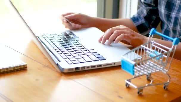 on-line bankovnictví, obchodní koncepce. samičí ruka držící kreditní kartu a nákupy online. Nakupování online pomocí kreditní karty v domácím životním stylu, nákupní košík v popředí