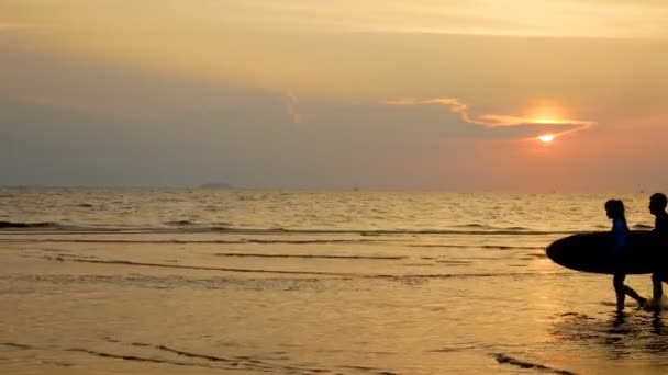 4K. silhouette of young happy surf man and woman running with long surf boards at sunset on tropical beach. surfer on the beach in sea shore at sunset time with beautiful light.