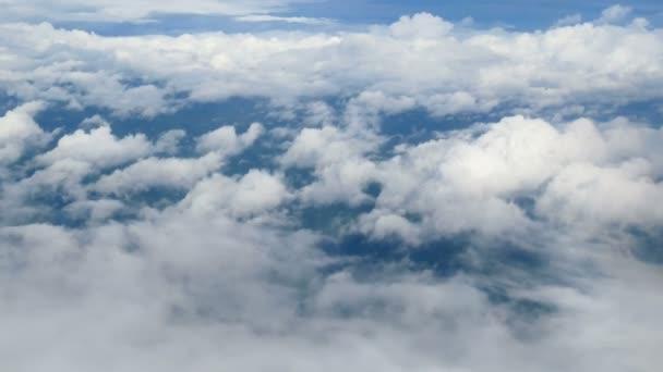 4 k. letecký pohled přes okno letadla. krásné bílé mraky na modrém nebeském pozadí. cestování letecky.