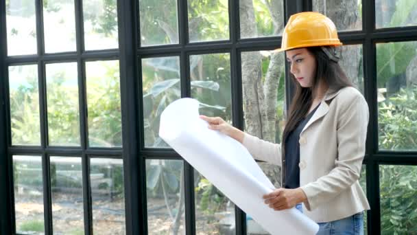 young Asian female construction engineer in a yellow hard safety helmet hat holding architect blueprints in hand, reading and checking on blueprint