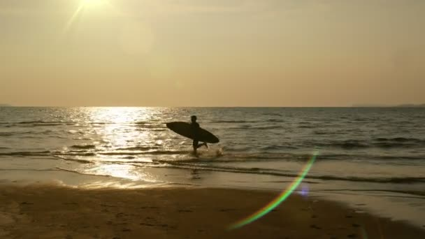 silhouette of young happy surf man running with long surf boards at sunset on tropical beach. surfer on the beach in sea shore at sunset time with beautiful sunlight flare. water sport activity