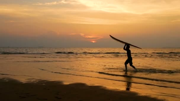 4K. silhouette of young happy surf man running with long surf boards at sunset on tropical beach. surfer on the beach in sea shore at sunset time with beautiful sunlight reflect on water surface.