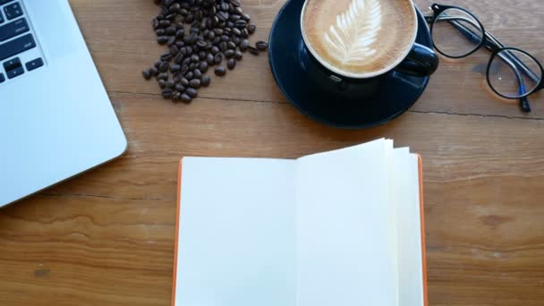4k. Blank fehér könyv a fából készült asztal, oldal flip széltől. könyv a munkahelyen a notebook, csésze kávé és poharak