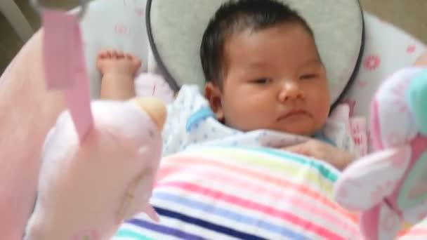 Riprese 4k, adorabile bambino asiatico si sentono assonnati , sdraiato in una culla swing