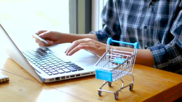 online banki, vásárlási koncepció. a női kéz a bankkártyával és online vásárlás. online vásárlás bankkártyával otthon életmód, bevásárlókosár az előtérben