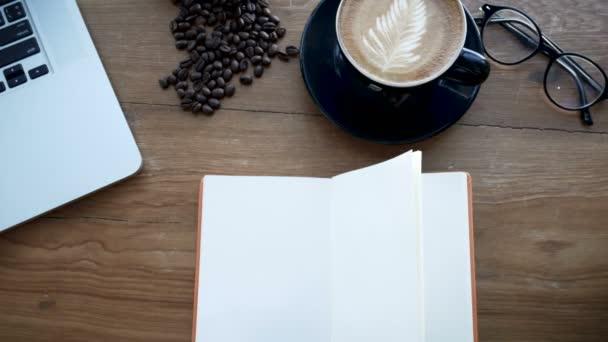 4k felvételeket cinemagraph. üres fehér könyv a fából készült asztal, oldal flip széltől. könyv a munkahelyen a notebook, csésze kávé és poharak