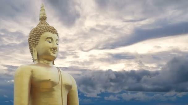 Velká silná socha Buddhy ve zlatých barvách s nádherným časovým odstupem oblohy, která je zatažená při západu slunce nebo východu slunce na pozadí. Obrázek Buddhy pro buddhisty