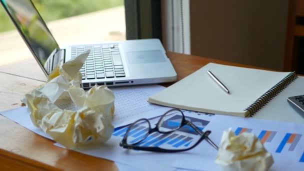 plný HD záběry pozadí pracovního prostoru. přenosný počítač s papírem jako účet grafů a grafů s kalkulačkou na pracovní ploše.