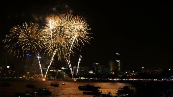 4k záběry skutečných ohňostrojů na obloze na oslavu v noci s výhledem do města na pozadí a lodí plovoucí na moři v popředí na pobřeží