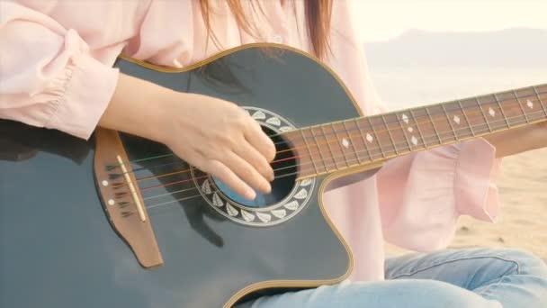 4k. blízko dlouhé vlasové ženy hrající na pláži akustickou kytarou s mírným větrem v době západu slunce, pocit relaxace