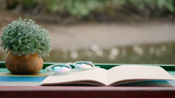 4k. cinemergh prázdné knihy s květináčem na dřevěném stole proti šumivého pozadí řeky