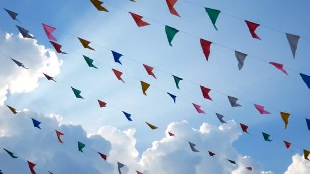 4k. színes design dekoráció háromszög szép zászlók fúj a szél lógott a kék ég háttérben a szórakoztató fesztivál Party esemény, ünnep ünnepe ünnep, karneváli fesztivál esemény.