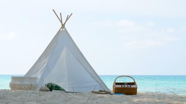 4k. romantikus fehér piknik sátor kosár élelmiszer fehér homokos tengerpart kristálytiszta víz és a kék ég a háttérben, az óceán hangja is