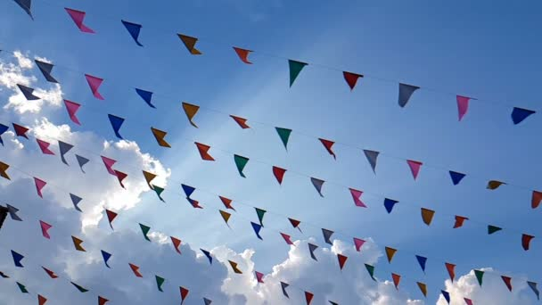 4K. slow motion of colorful design decoration triangular fair flags blowing on the wind hanging on blue sky background for fun festival party event, feast celebration holiday , carnival festival event.