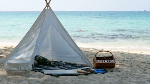 4k Romantický bílý stan s jídlem na bílé písečné pláži s křišťálově čistou vodou a modrou oblohou na pozadí