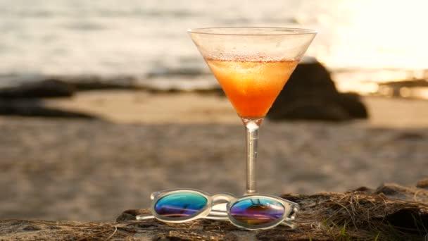 4k. koktélpohár vízcseppekkel a tengerparton arany hullámú tükröződéssel bokeh fénnyel a naplemente idején