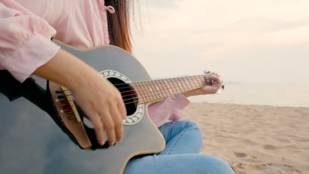 4K. close up of long hair woman playing acoustic guitar at the beach with gentle wind during sunset time, feeling relax