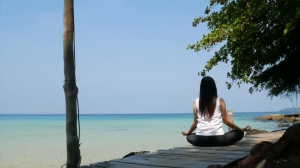 4k. zadní strana asijské ženy cvičit koncentraci s meditací sedí na dřevěném mostě přes moře během letních prázdnin.