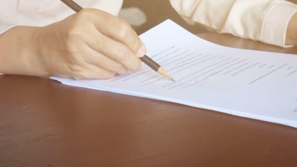 4k. Frau liest auf Papier, blättert Seite und benutzt Bleistift, um Text auf Dokument zu markieren
