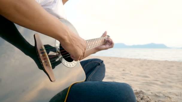 4k. poblíž muže, který hraje na pláži při západu slunce akustickou kytarou, cítí relaxaci