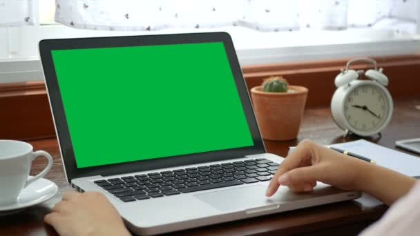 4k. Nahaufnahme Frau, die mit Laptop-Computer arbeitet, mit dem Finger mit Tastatur und Touchpad oder Trackpad für Dia. Computer-Laptop mit leerem grünen Bildschirm Chroma-Schlüssel.