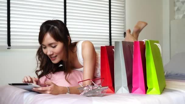 Krásná Asijská děvčata v ložnici, nadšená používáním tabletu, online nakupování, hledáním informací a výhodnou koupí věcí. Koncepce životního stylu a elektronického obchodu