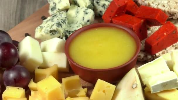 Sýrová deska s několika odrůdami z ovoce a medu.
