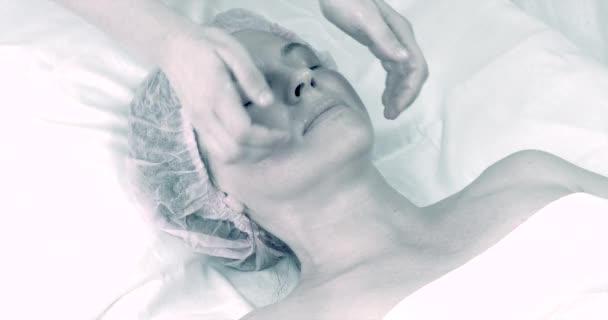 Krásná dospělá žena, která dělá masáž obličeje v salonu krásy.