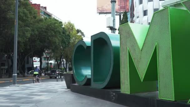 Pohled na zelené CDMX písmena na ulicích Mexico City s auty a stromy v pozadí