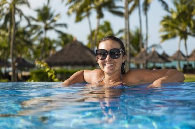 Beautiful brazilian woman enjoying vacation holidays at luxurious beachfront hotel resort with swimming pool and tropical lansdcape near the beach