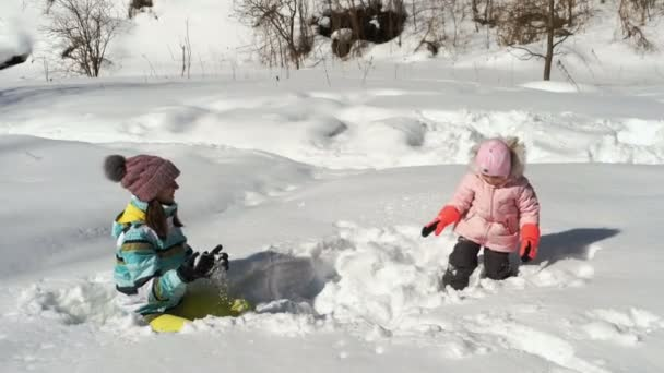 Frau und kleines Mädchen spielen mit Schnee