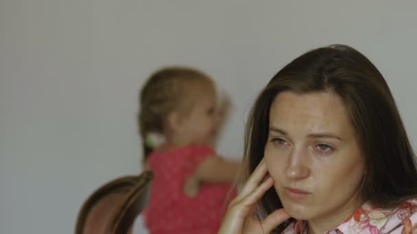 Ritratto della madre sconvolta con fastidiosa bambina bambino sullo sfondo