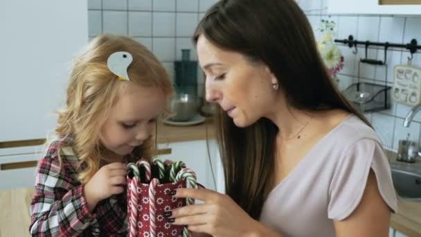 Žena s malou holčičku s vánoční cukrové třtiny hrát