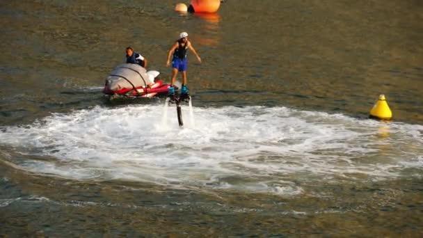Muž na koni jet fly deska v tyrkysové vodě při západu slunce