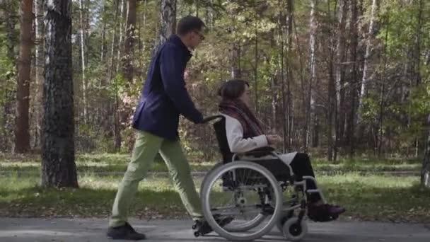 Frau im Rollstuhl geht mit Freund spazieren