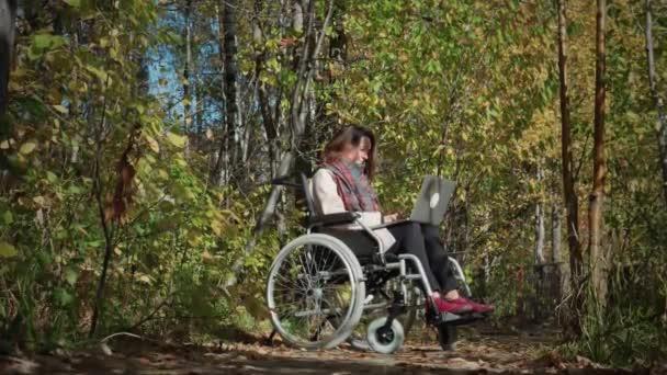 Behinderte Frau benutzt Laptop im Freien