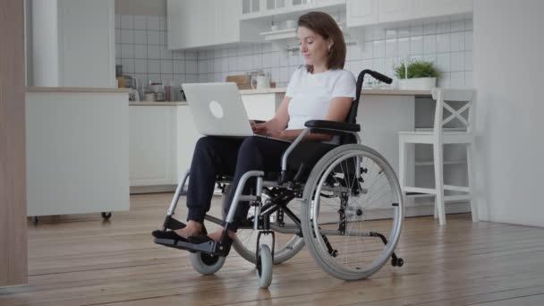 Behinderte Frau im Rollstuhl benutzt Laptop
