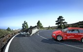 Two cars accident. Crashed cars on a road in the country side location. A red sedan against a silver car upside down. Strong collision with big damages.