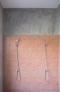 Two modern faucets in semi outdoor shower room for fitness or gym