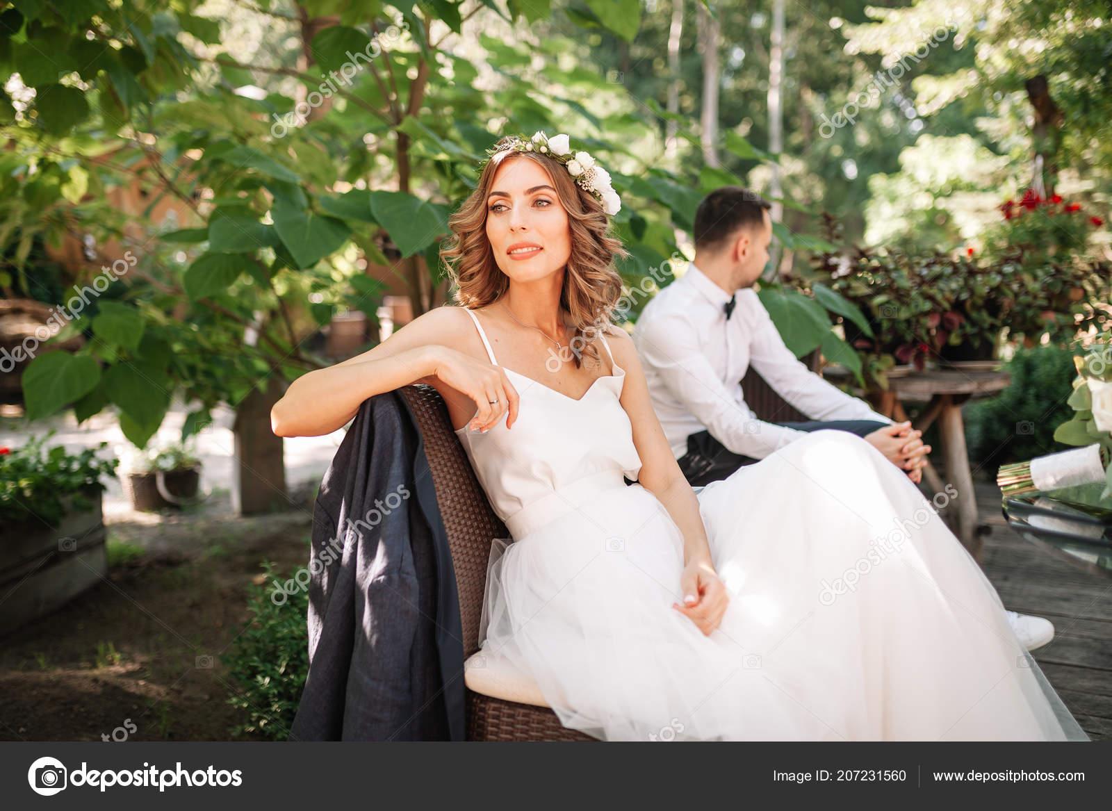 d1a8e7ffe2ce Una bella sposa in un abito da sposa bianco e la corona si siede su una ...