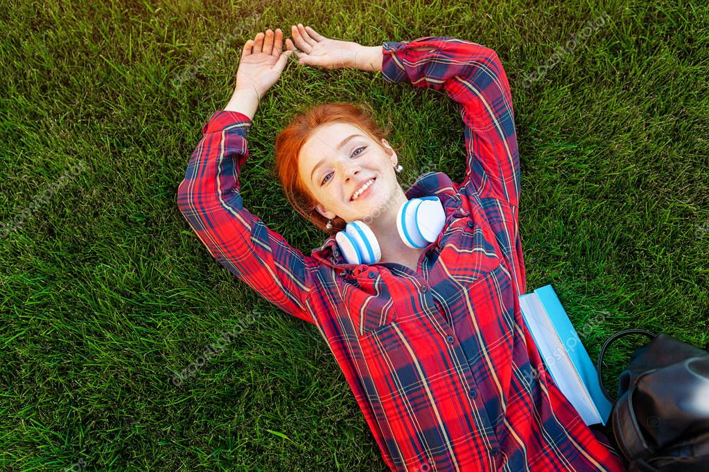 Beautiful young red-haired student girl with freckles lying on her back on grass and lawn view from above. Dressed in a red checkered shirt, resting after classes