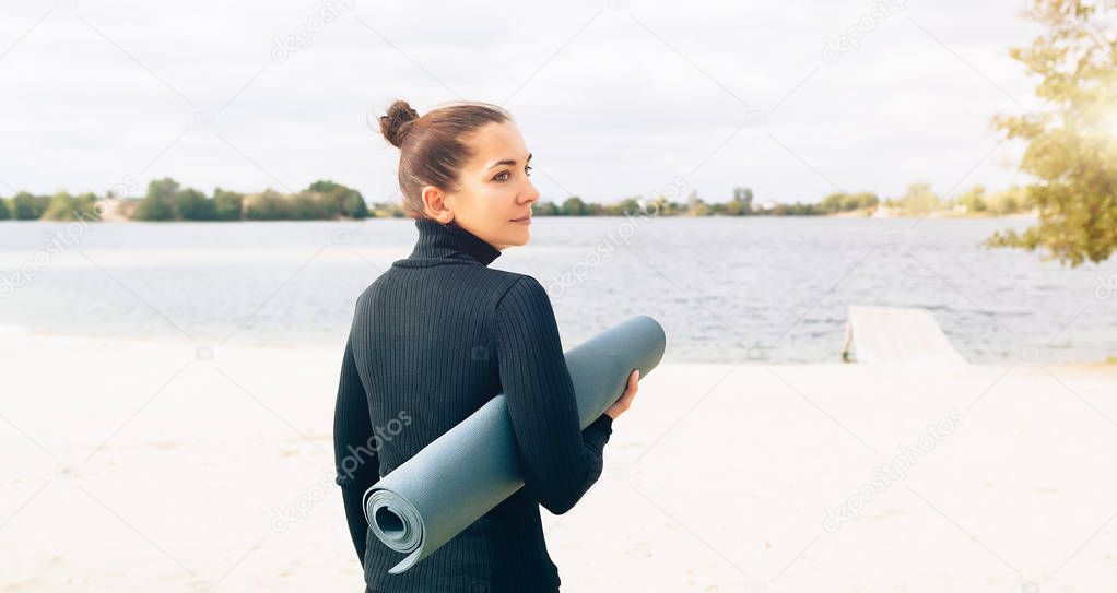 An athletic woman is standing with her back to the camera on the lake shore and is holding a yoga mat.