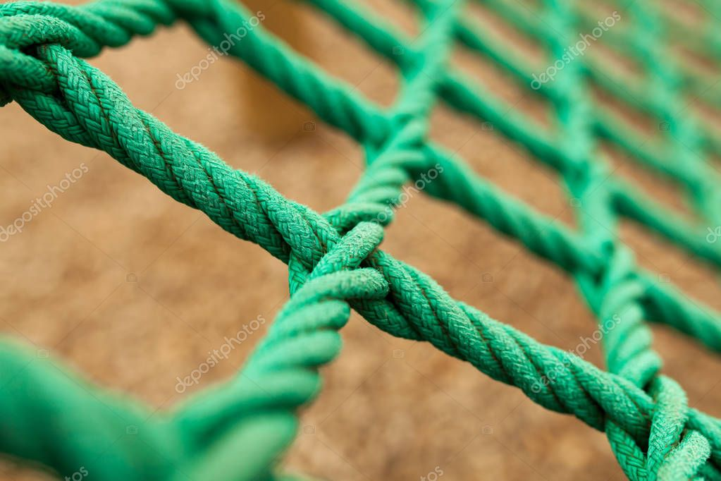 Rope mesh with blurry background. It is a green rope mesh in a playground. It is not a brand new rope mesh but it is old and deteriorate.