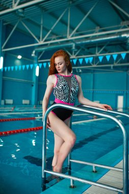 A beautiful red-haired girl stands on the steps of the swimming pool ladder. A woman is engaged in a healthy lifestyle. Water training