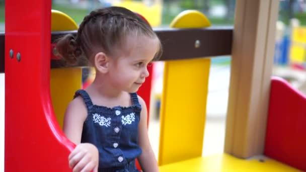 Malá holčička na hřišti. Dítě, které si v létě hraje venku. Šťastné dětství.