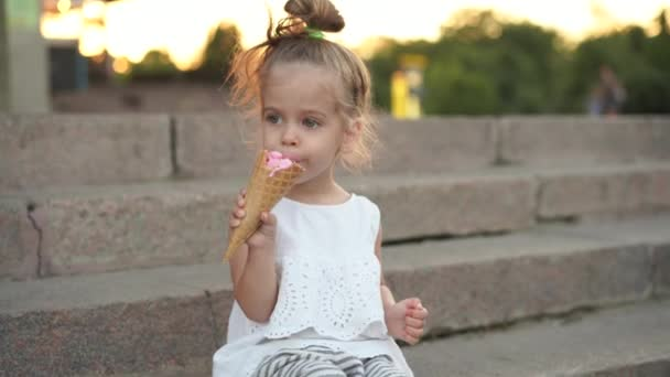 Cute caucasian little girl enjoys ice cream in a waffle cone walking in the park. The child eats bright ice cream