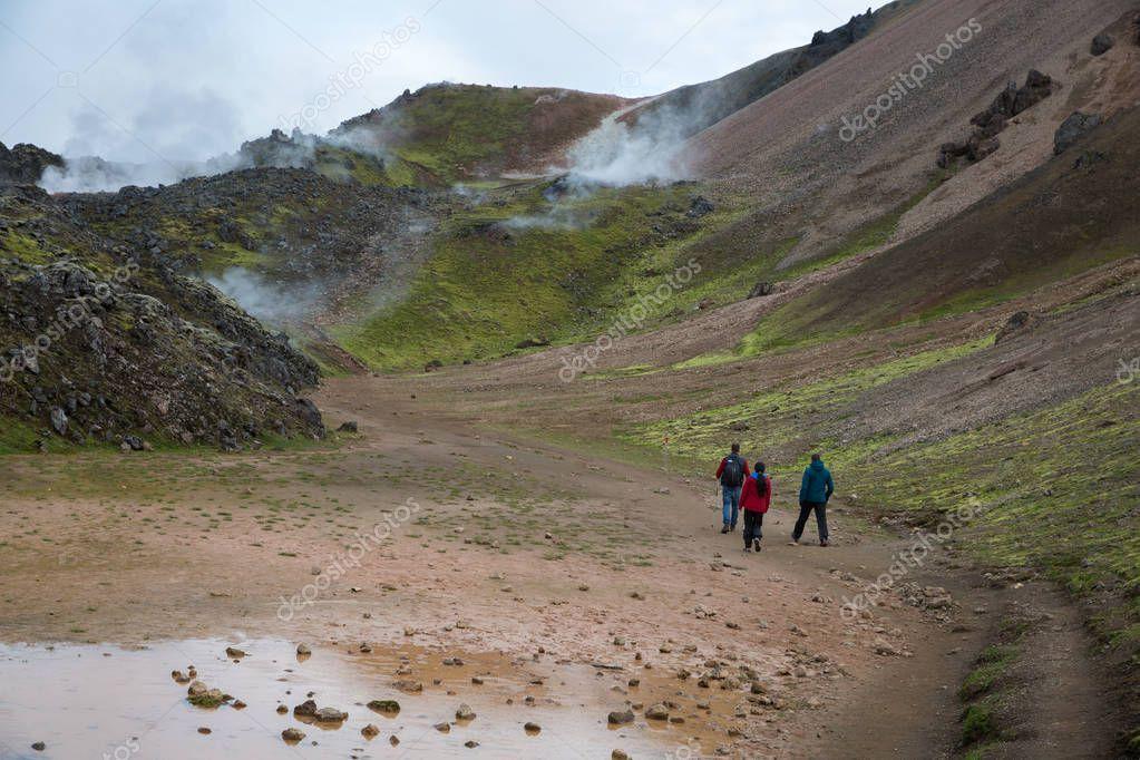 Tourists walking through the steaming mountains of Landmannalaugar