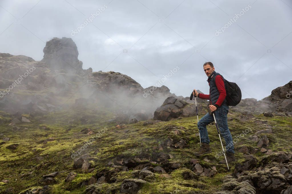 A man with trekking poles walks over the smoking rocks of Landmannalaugar